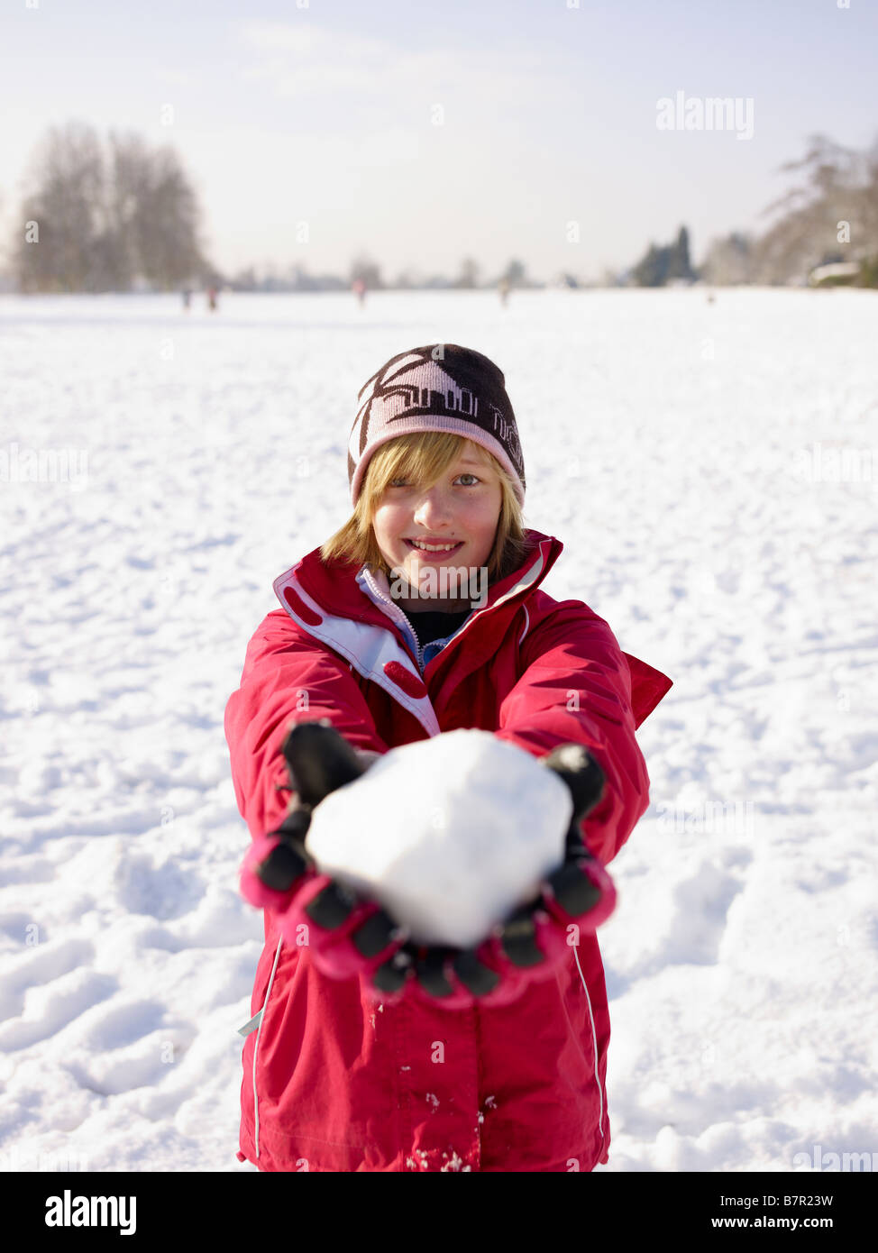Girl holding a snowball on a snowy day Redbourn Hertfordshire England UK - Stock Image