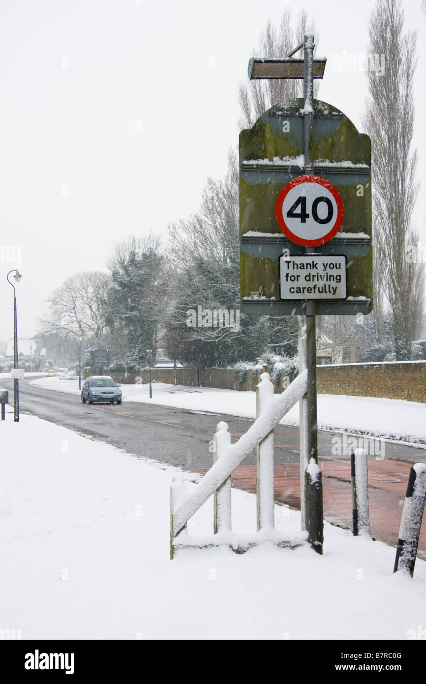 A snowy English village scene with a 40mph speed limit sign and thank you for driving carefully sign.  Berkshire, - Stock Image