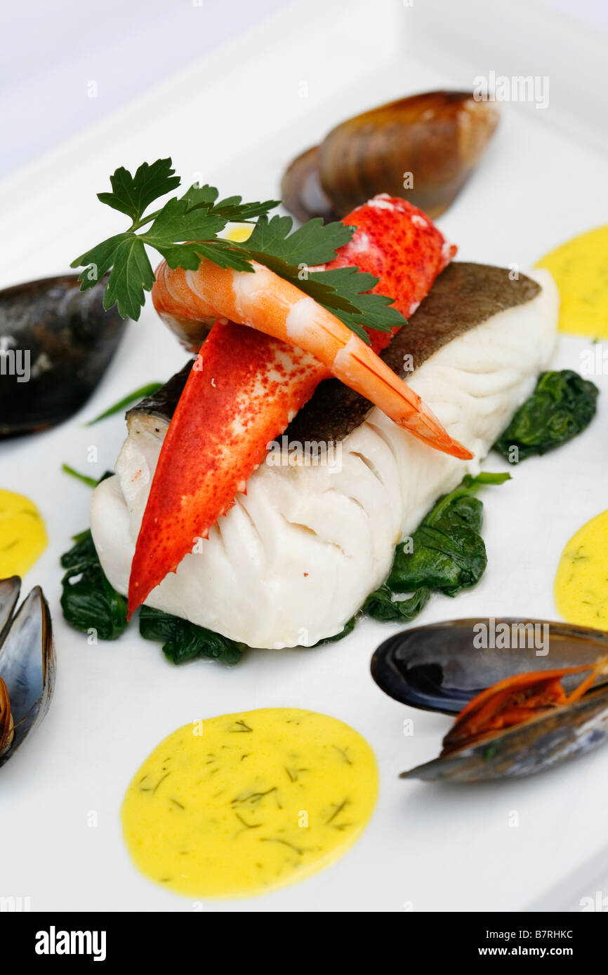 sea bass on a bed of spinach with mussles and lobster claws - Stock Image