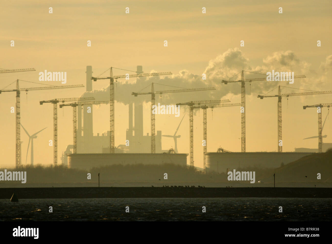 Many cranes and chimney pouring plumes smoke silhouette evening sky horizon Rotterdam Europort Europoort Netherlands - Stock Image