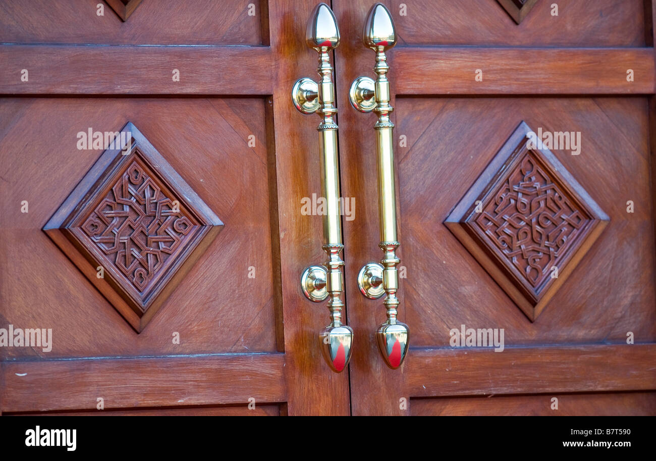 Ornate wooden exterior door and brass handles, Dawoodi Bohra Mosque,  Northolt, London UK - Stock Image