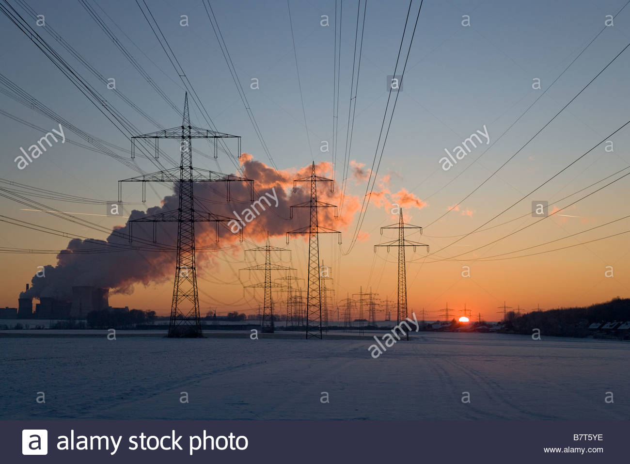 power plant exhaust CO2 emission high voltage transmission towers winter sunset dusk snow energy crisis Neurath - Stock Image