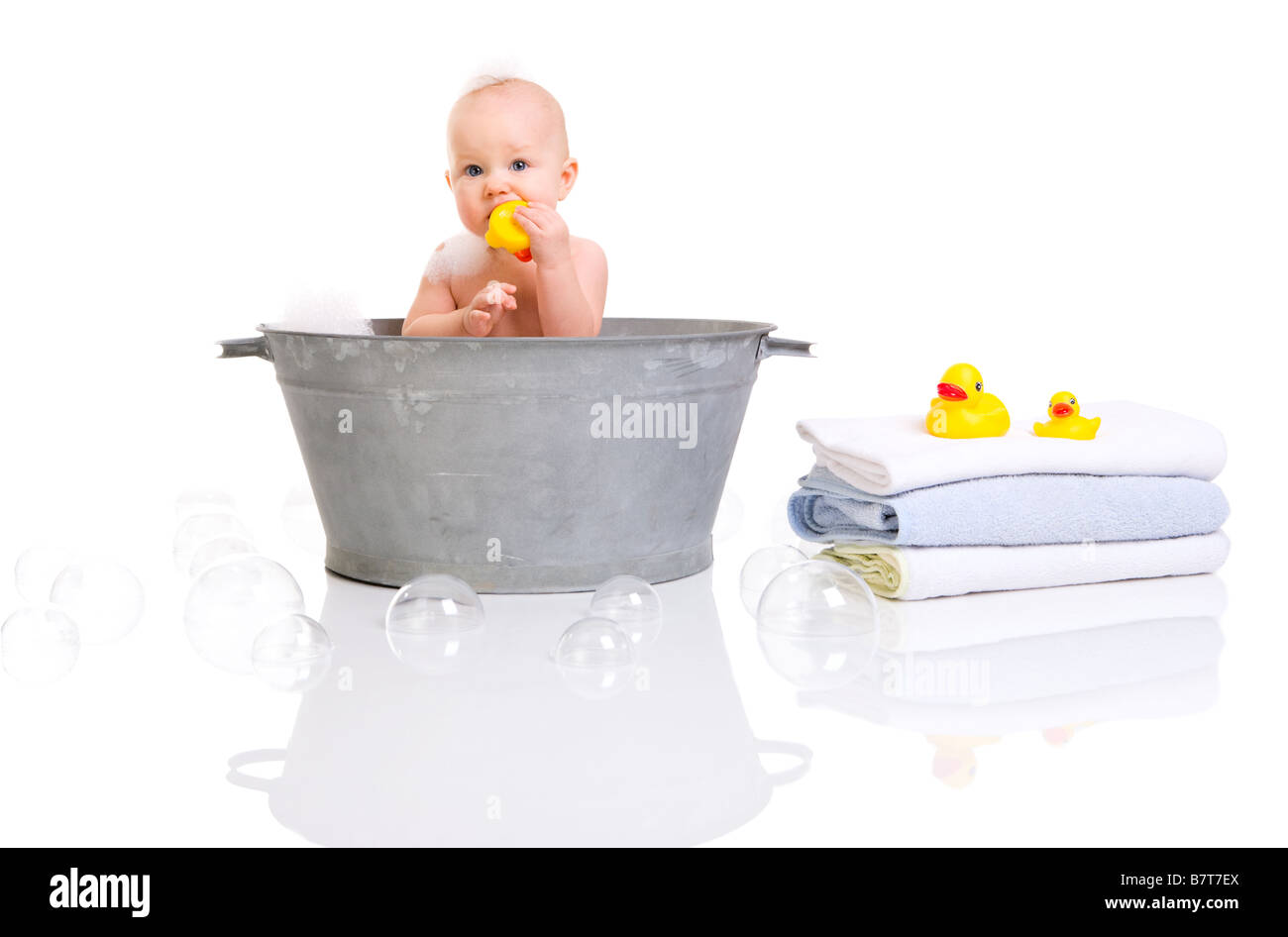 Bath Time Cute happy baby girl having bath Isolated on white - Stock Image