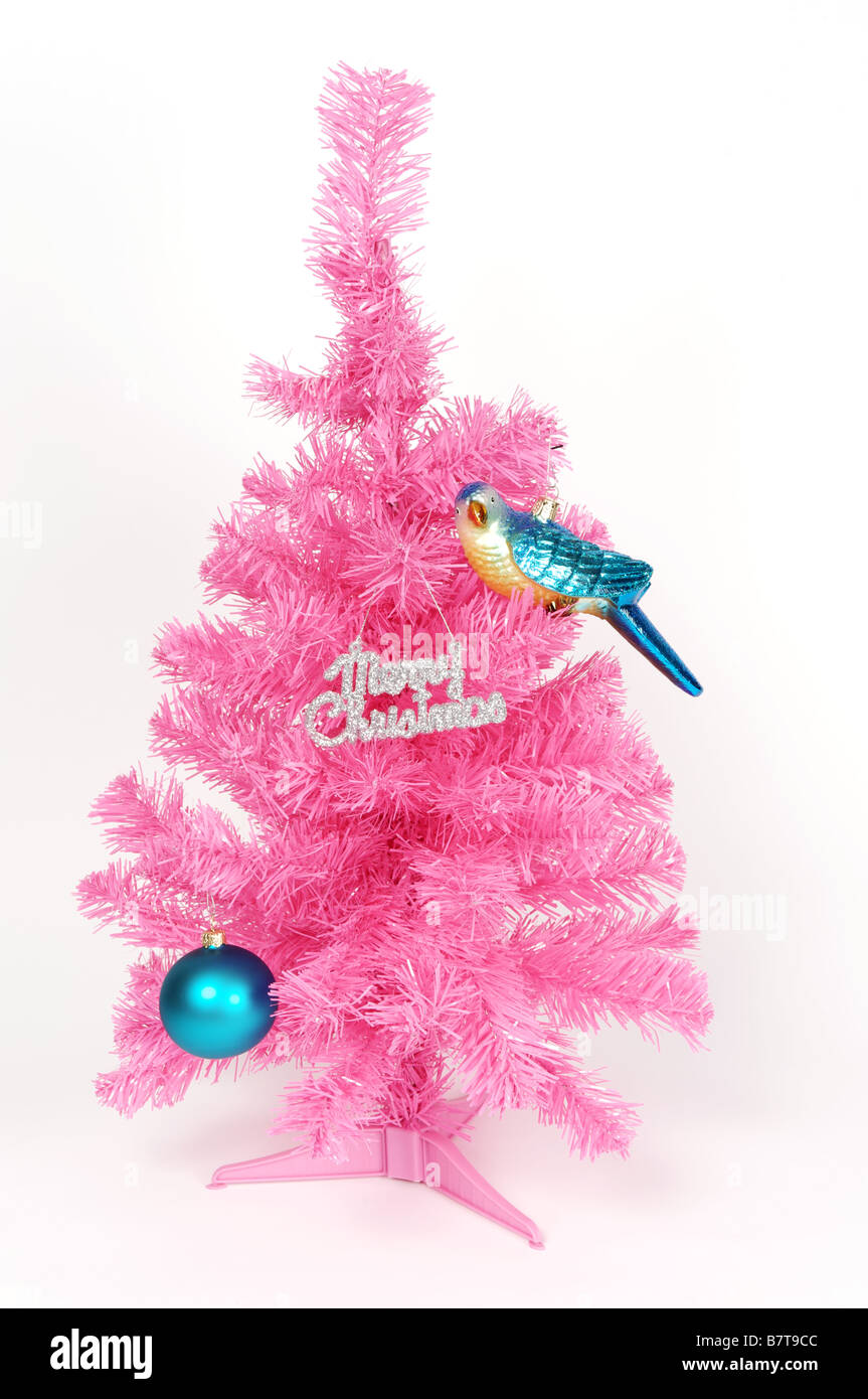 Pink plastic Christmas tree with shiny bauble, bird decoration and Merry Christmas sign. - Stock Image