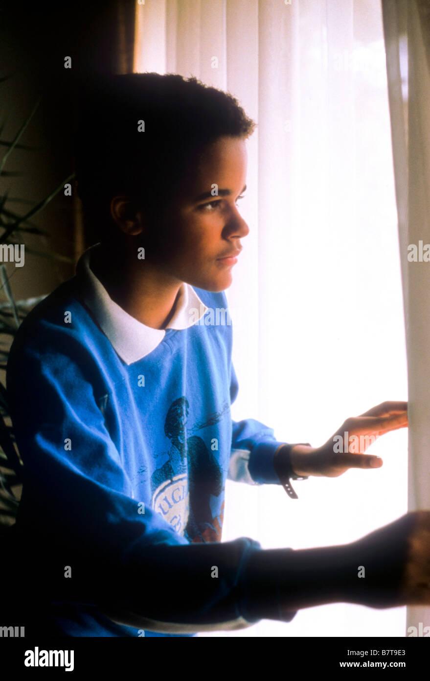 Black Teen Boy Looks Sad And Worried As He Looks Out Window Stock Photo Alamy