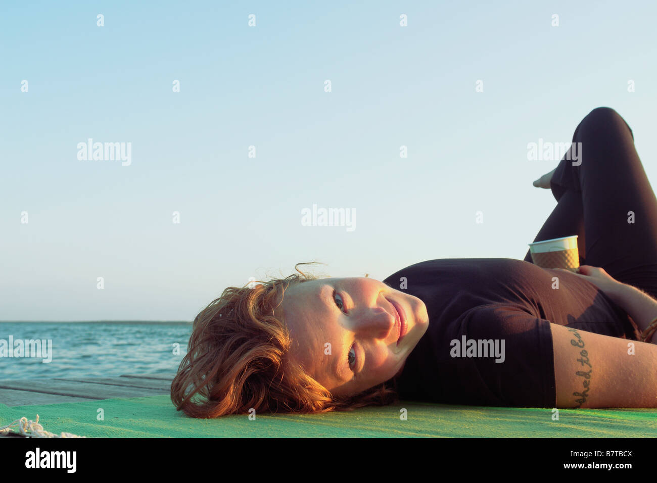 Woman lying on dock by lake, Clear Lake, Riding Mountain National Park, Manitoba, Canada - Stock Image