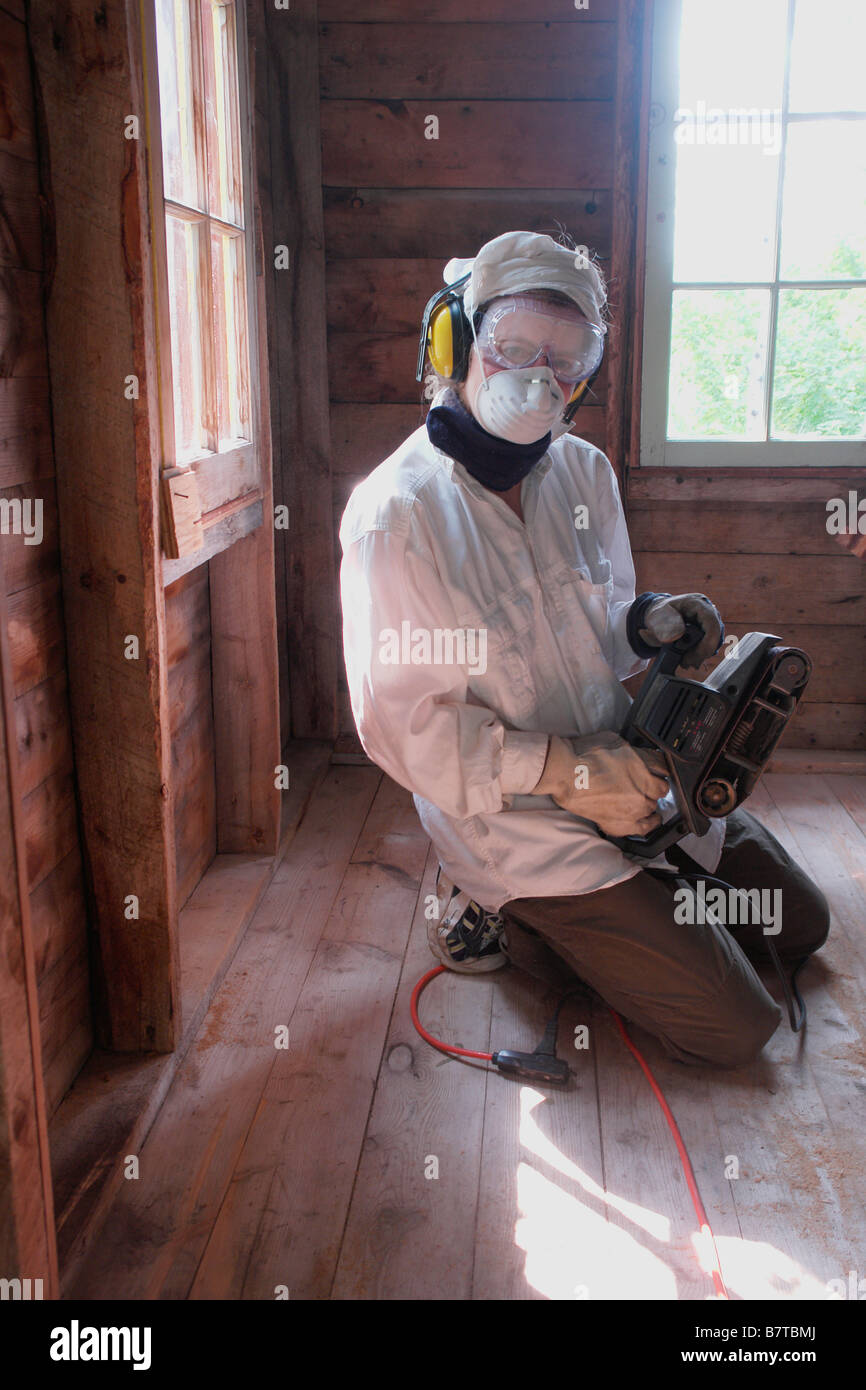 Person with protective gear holding sander, Manitoba, Canada - Stock Image