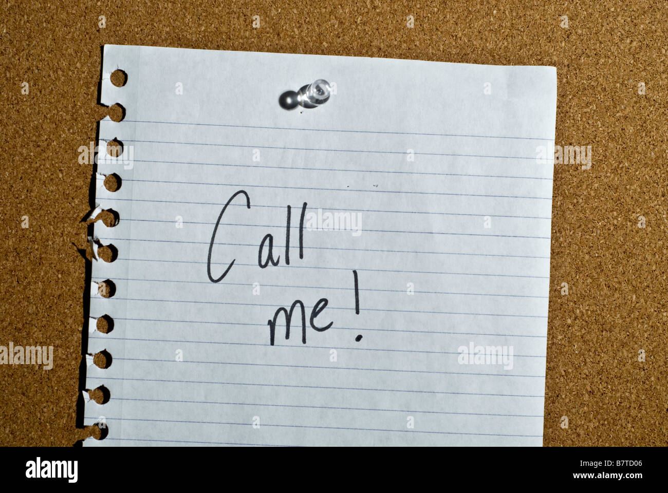 A post it note memo on a cork board that says call me. - Stock Image
