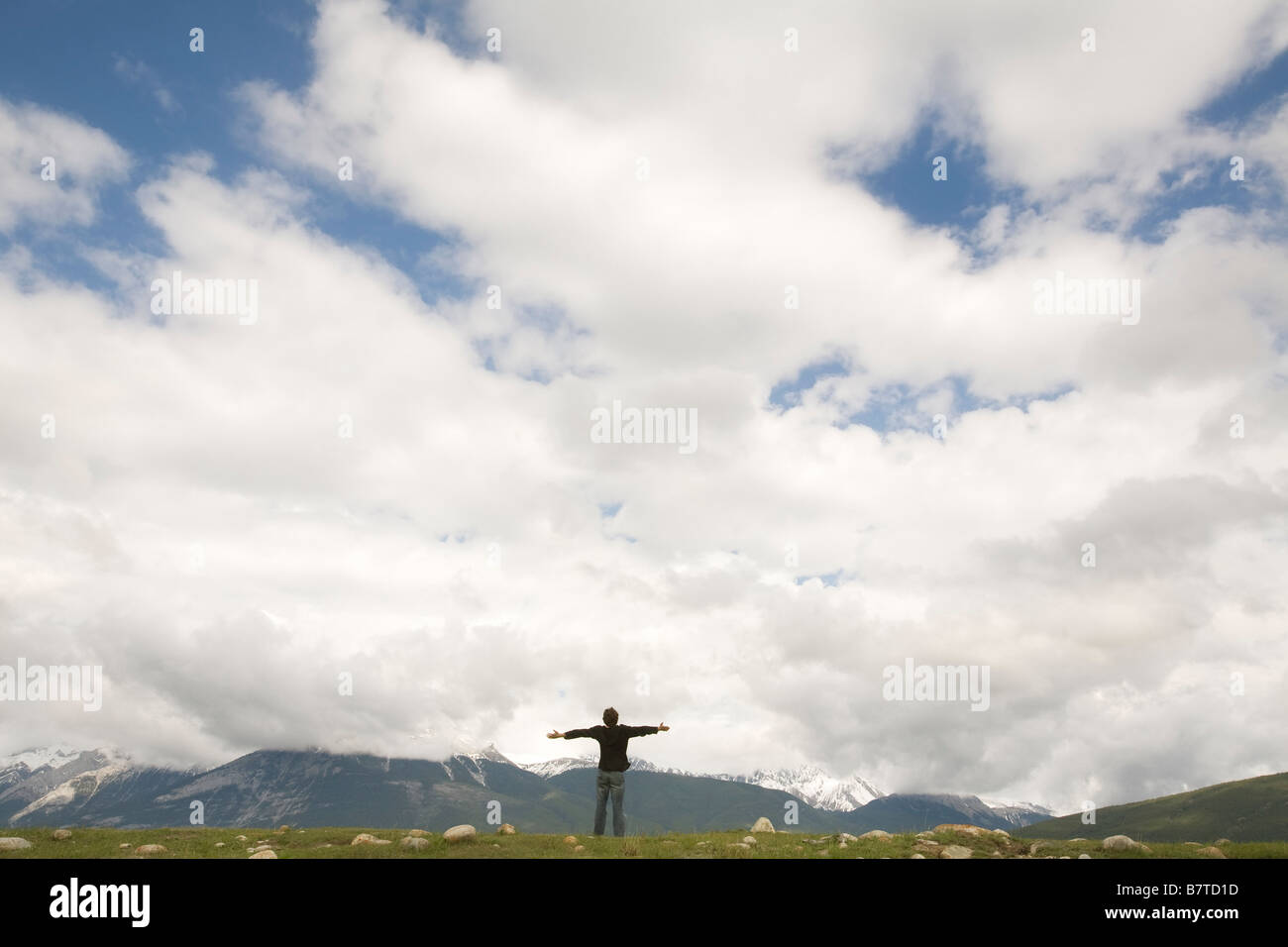 person on an hill with arms outstretched - Stock Image
