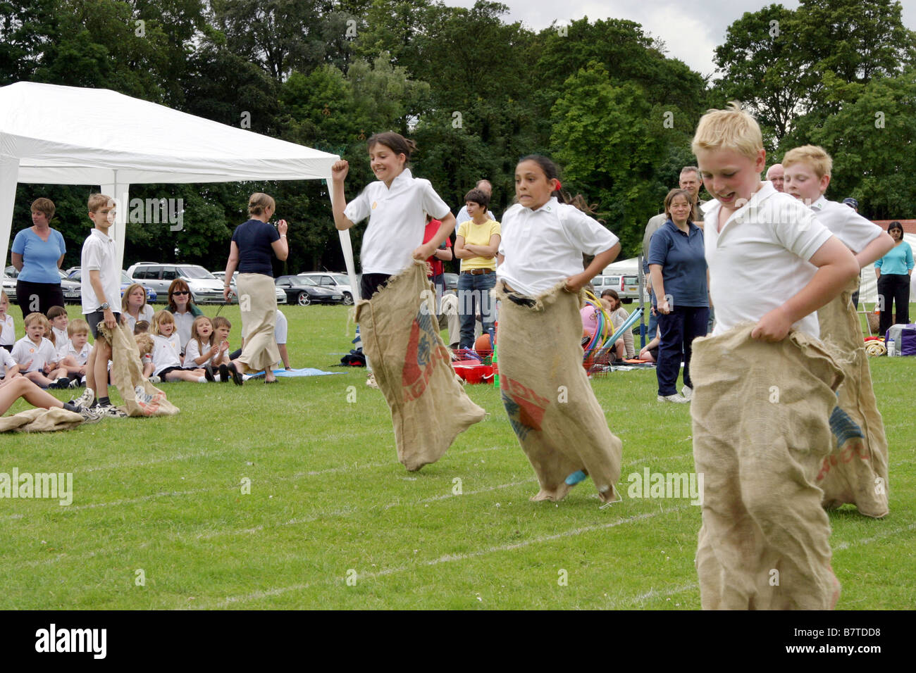 Children doing the sack race, Primary school Sports Day, UK - Stock Image