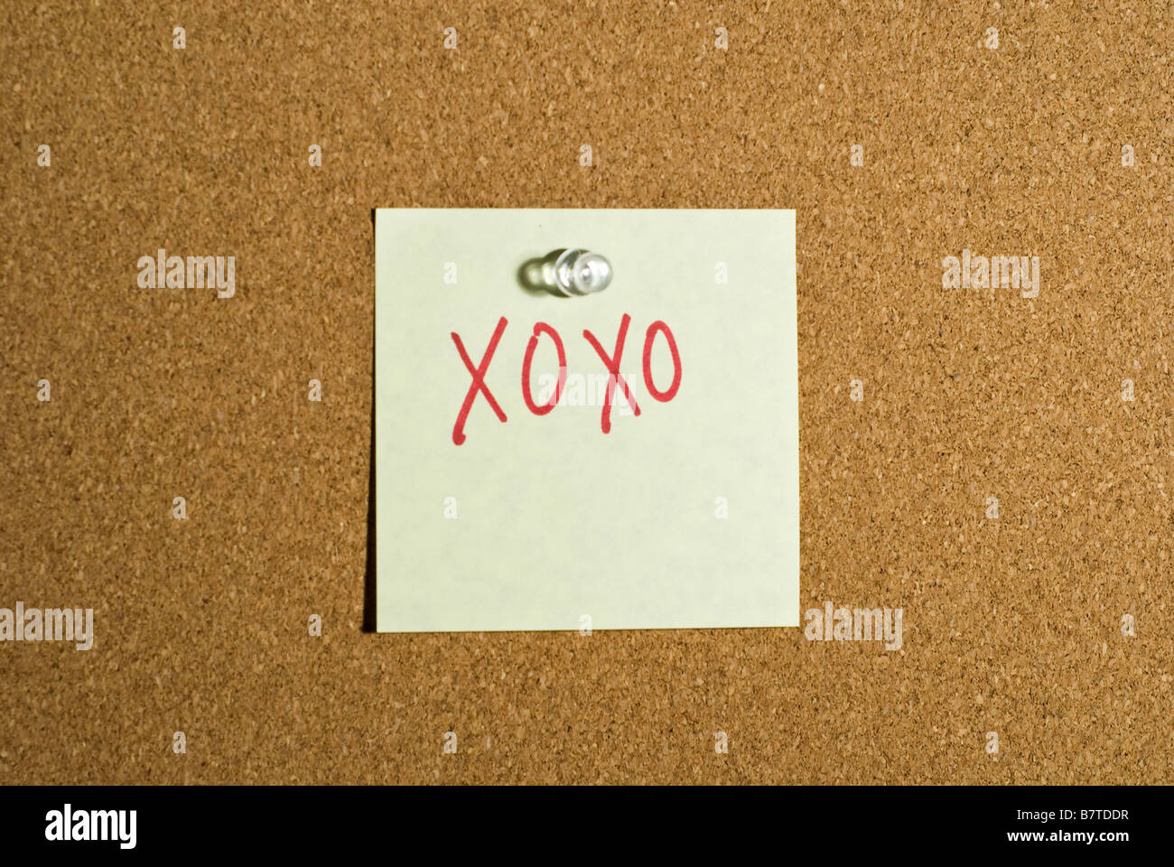 A post it note or memo on a cork board that says XOXO for hugs and kisses for Valentines's day. - Stock Image