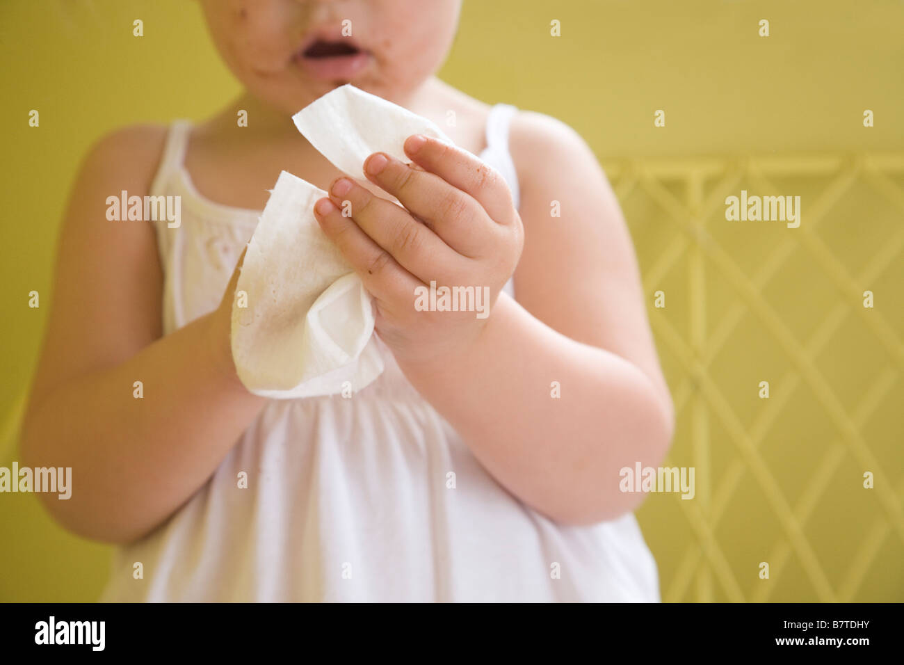 Little girl wiping her dirty fingers - Stock Image