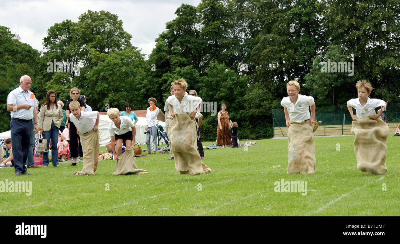 Children racing in the sack race, Primary school Sports Day, UK Stock Photo