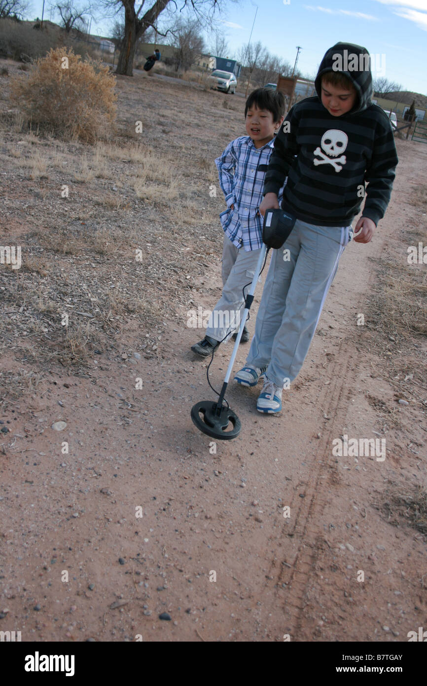 child using a metal detector on a field, walking with a friend in search of treasures - Stock Image