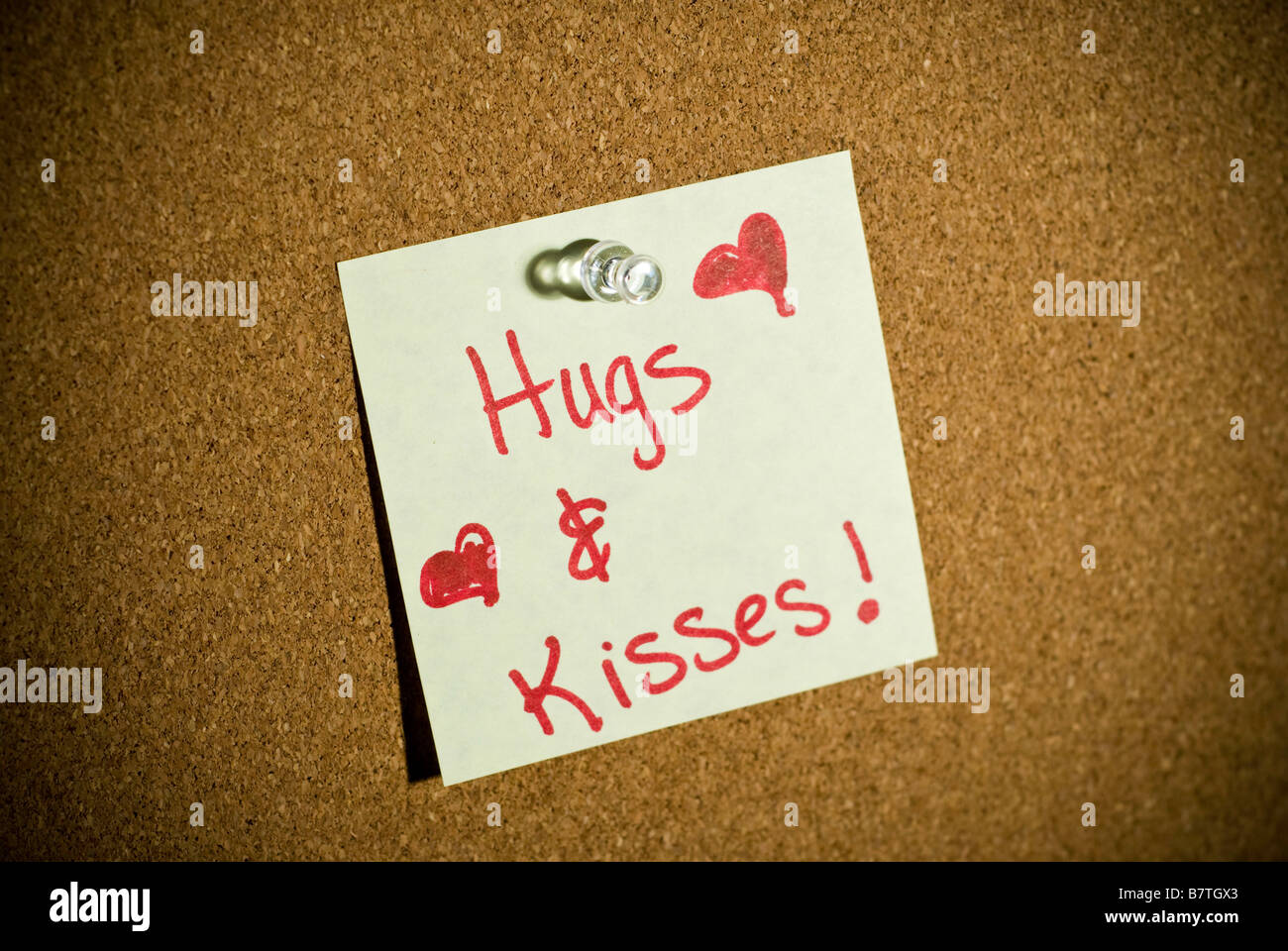 A post it note or memo on a cork board that says Hugs and Kisses for Valentines's day with hearts. - Stock Image