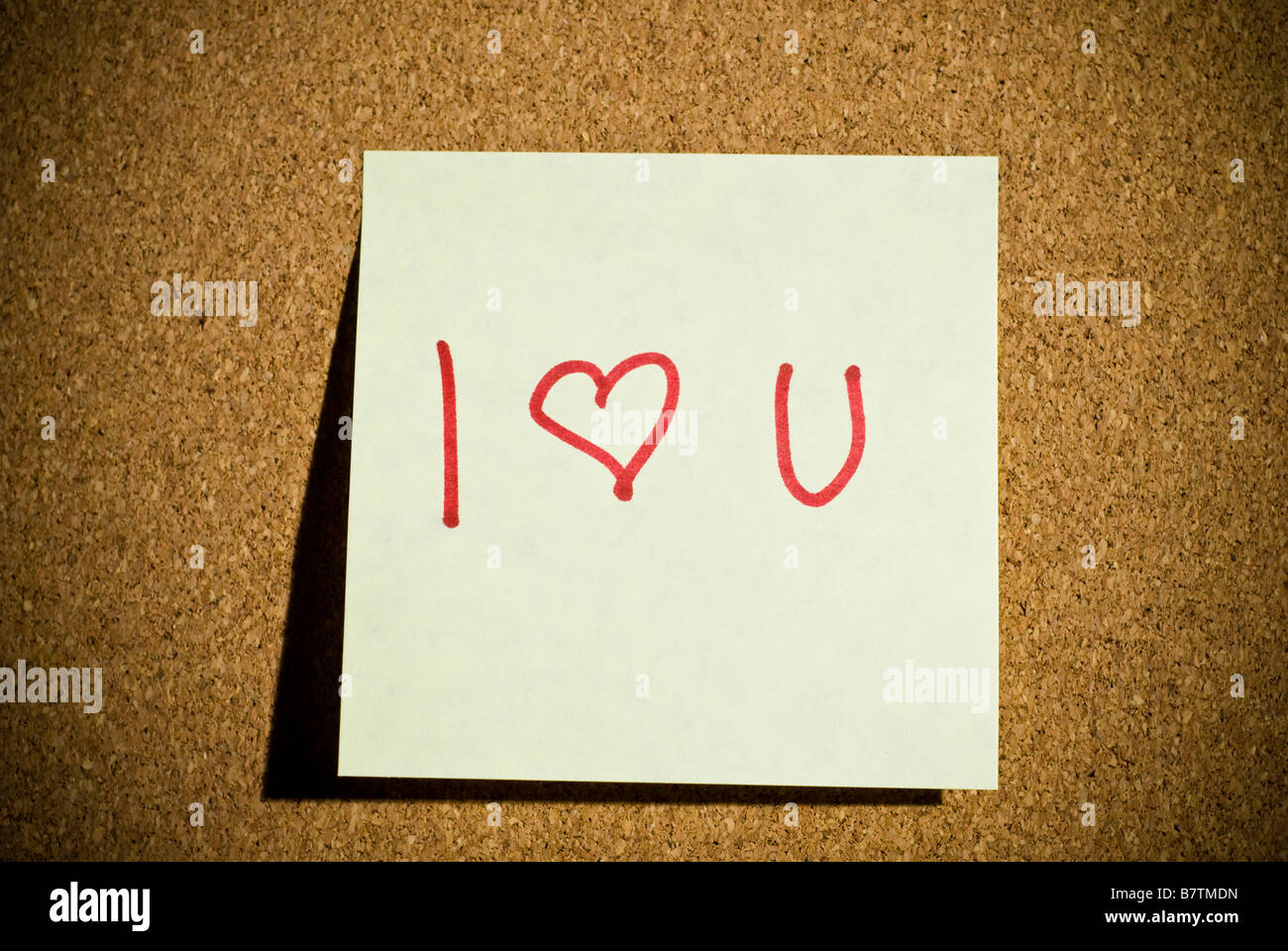 A post it note memo on a cork board that says I Love You with a heart. - Stock Image