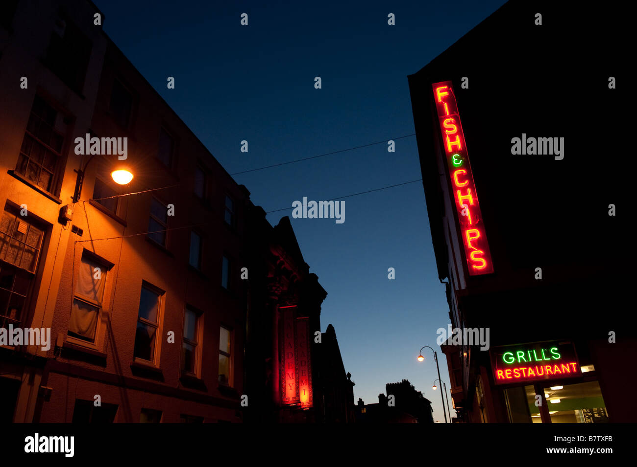 Fish and chips shop neon signs illuminated at night Aberystwyth Wales UK - Stock Image