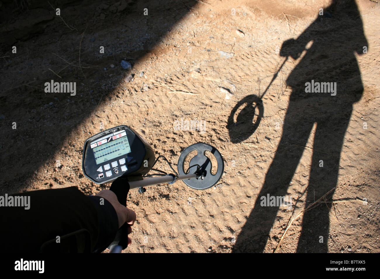 a person using a metal detector to look for coins - Stock Image