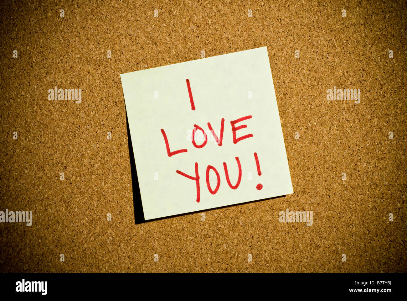 A post it note memo on a cork board that says I Love You. - Stock Image