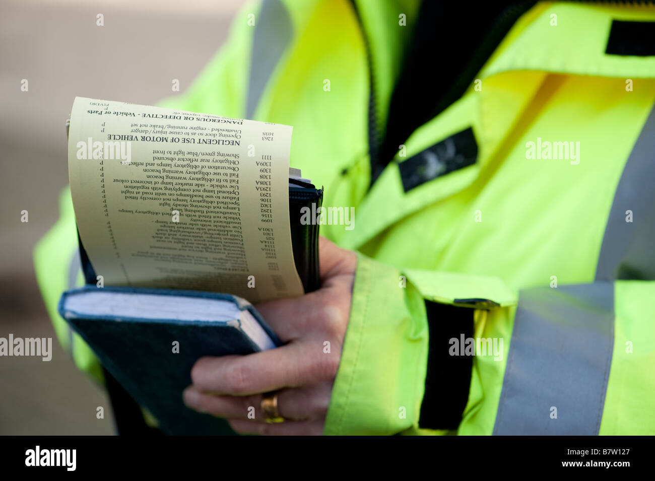 A UK traffic warden issuing a parking ticket for a car - Stock Image