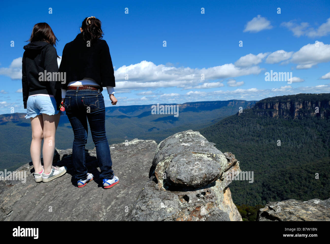 Tourists standing very tentatively near edge of cliff. Blue Mountains, Katoomba, Australia - Stock Image