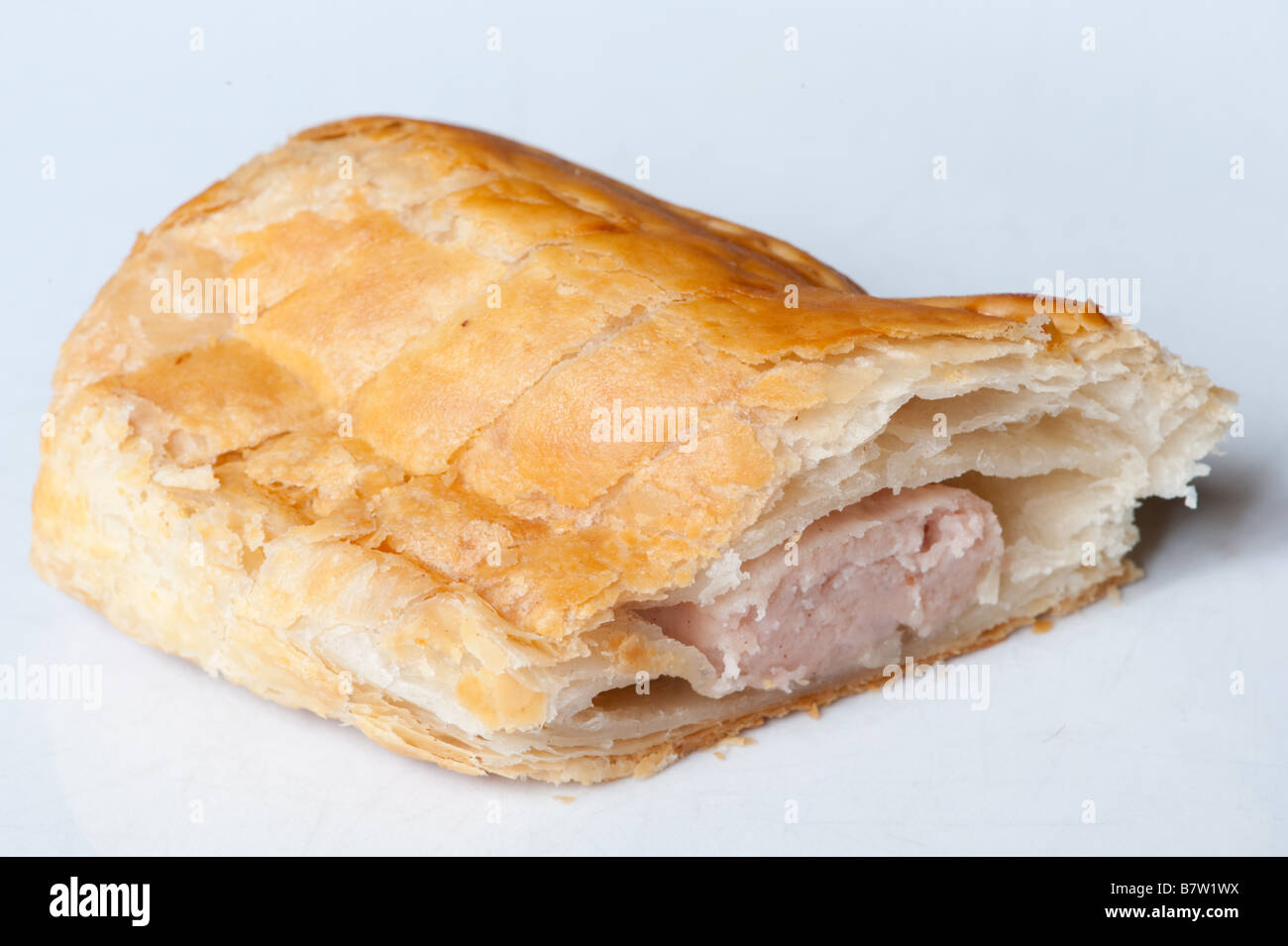a sausage roll cut in half on a white background - Stock Image