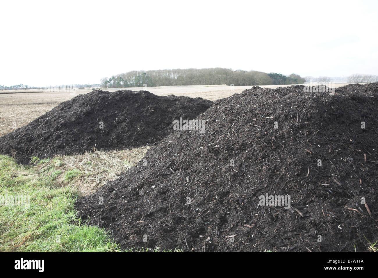 Pile of organic compost manure fertiliser by arable field Sutton Suffolk England Stock Photo