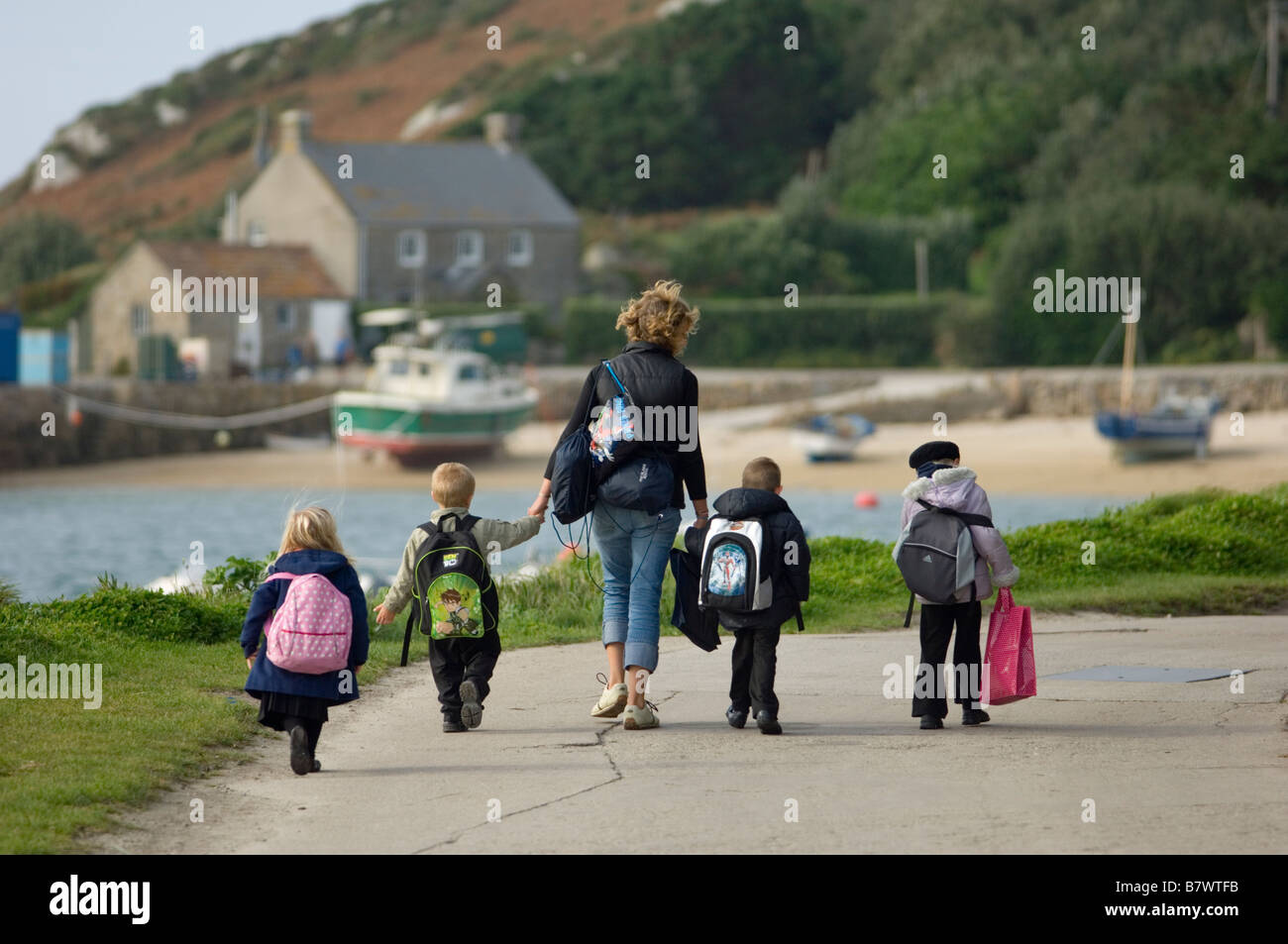 four local children accompanied by a young woman walk to New Grimsby Quay. Tresco The Isles of Scilly. Cornwall. - Stock Image