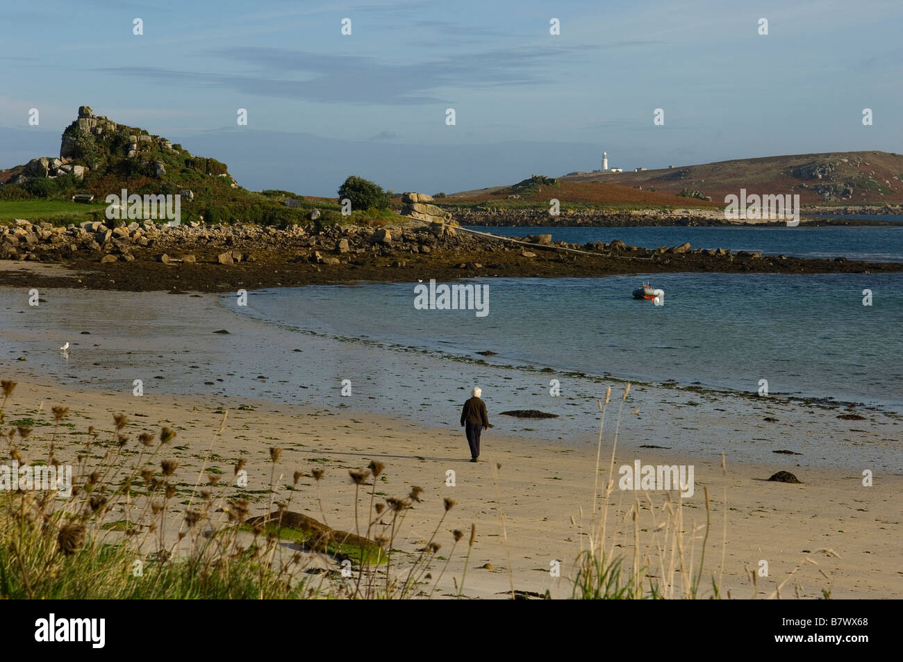 A woman walks along the empty beach at Old Grimsby. Tresco. Isles of Scilly. Cornwall. England. UK - Stock Image