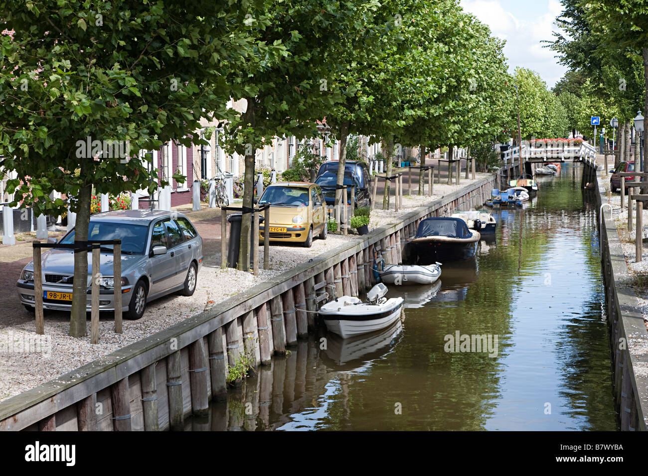 Canal with boats and cars parked alongside in residential area of Harlingen Friesland Netherlands - Stock Image
