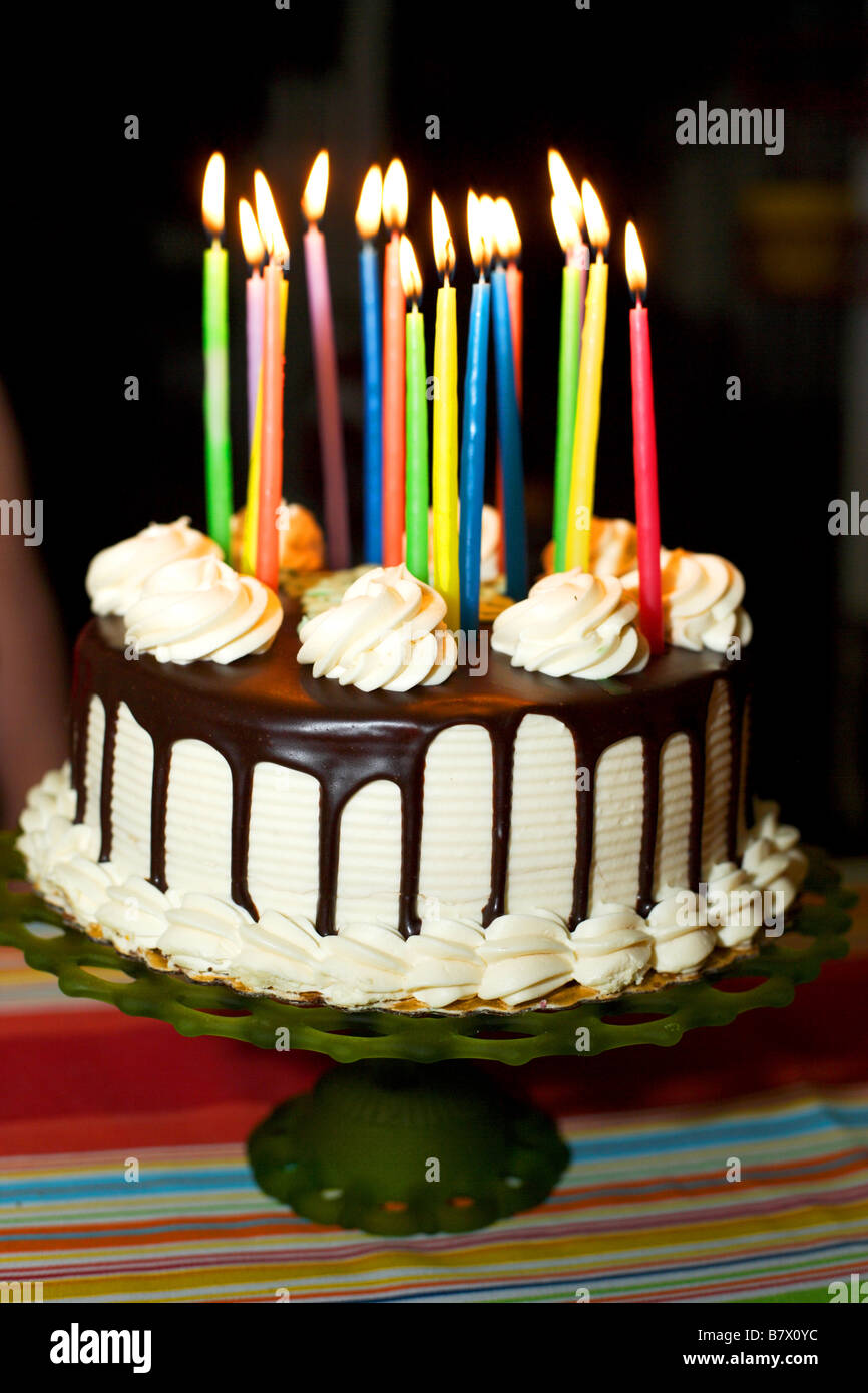 A birthday cake with lit candles white frosting and chocolate Stock