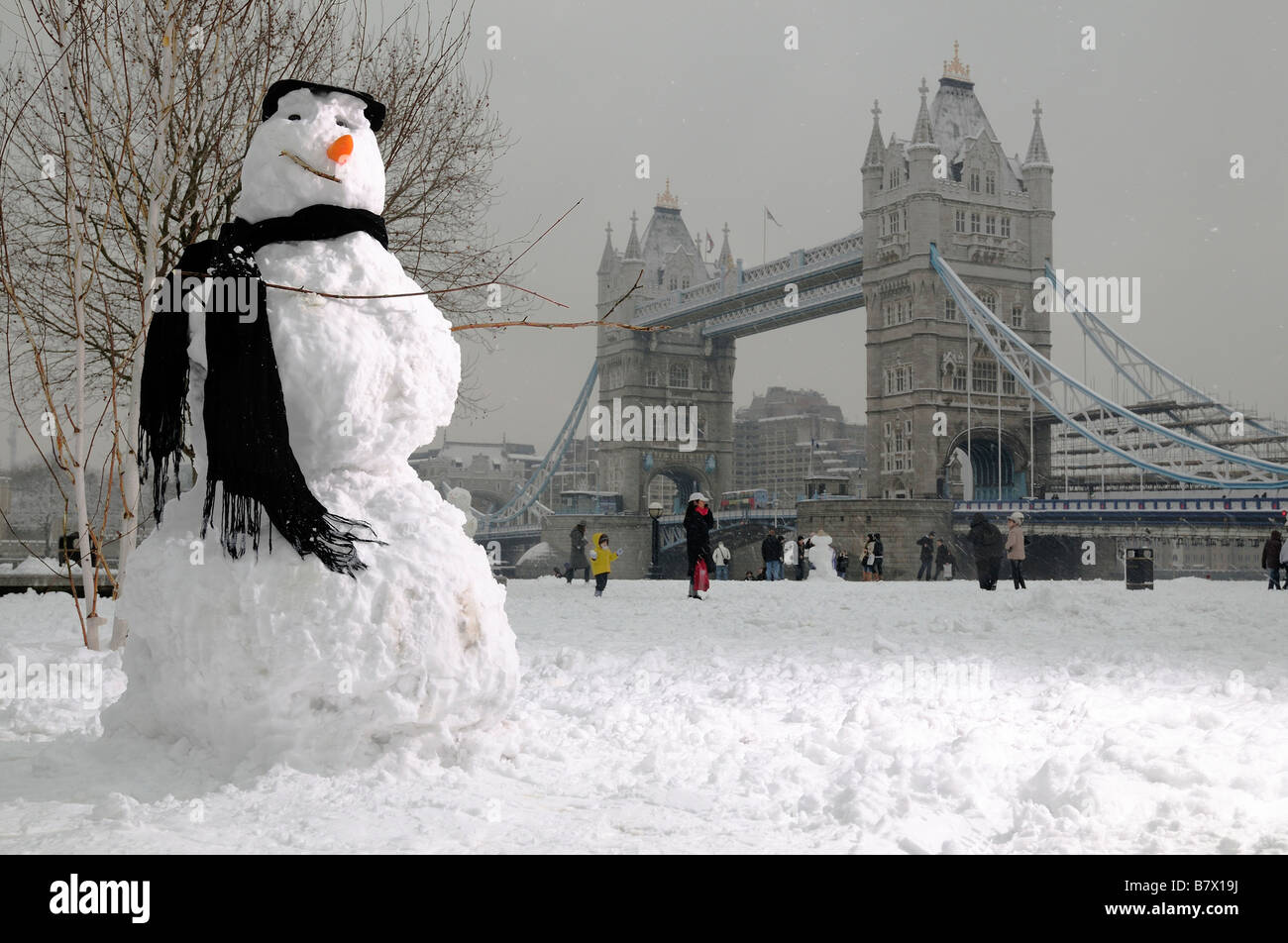 Heavy snowfall covers London - A snowman tourist visited Tower Bridge for this postcard. - Stock Image