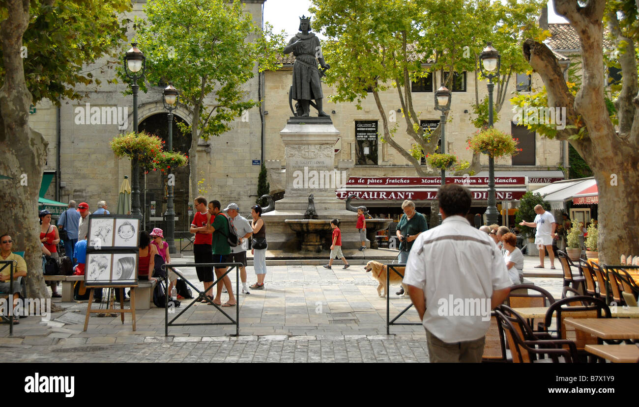 People in the medieval town square, Statue King Louis IX, Aigues Mortes, Camargue, France, Europe - Stock Image