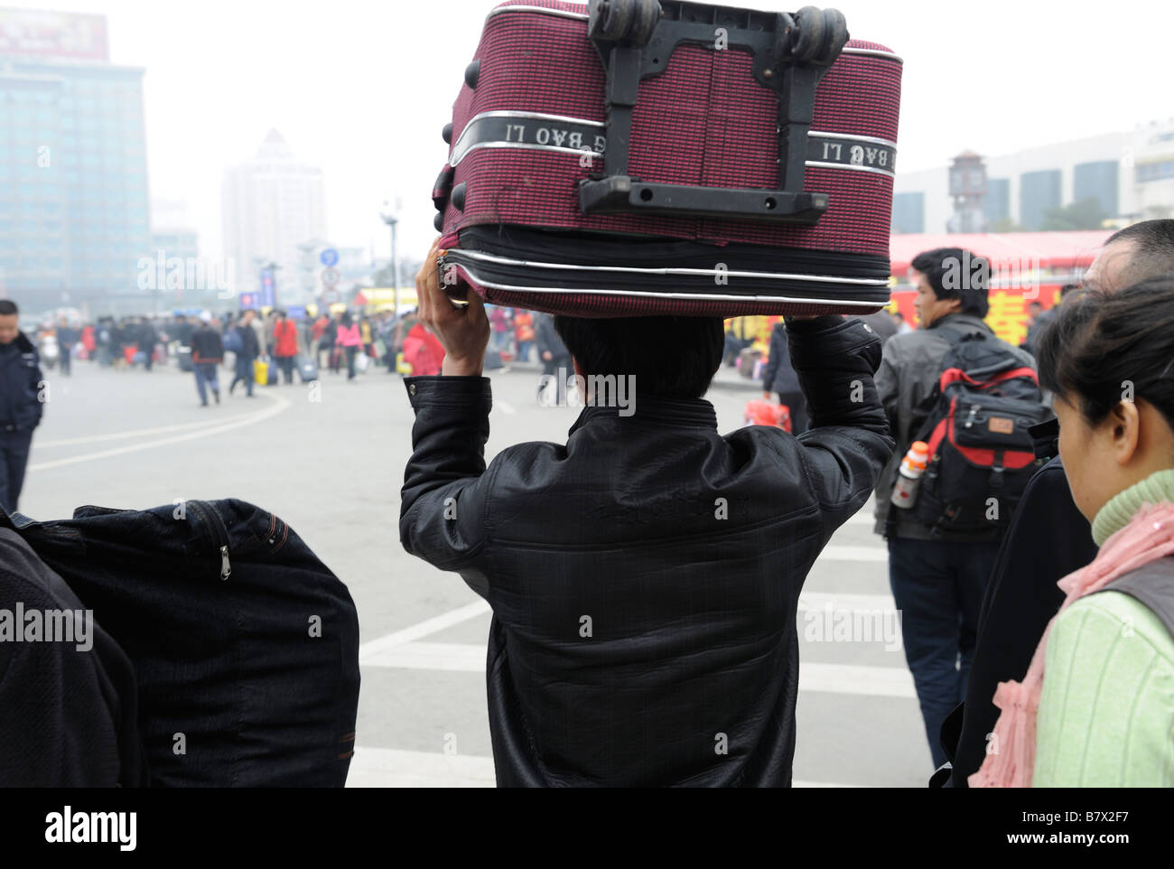 Migrant workers carry their luggage leaving the train station in Nanchang, Jiangxi, China. 05-Feb-2009 - Stock Image
