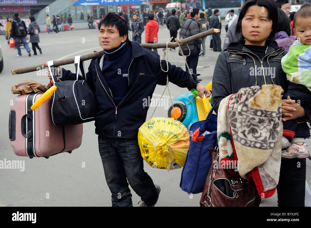Migrant family members leaving the train station of Nanchang, Jiangxi, China. 05-Feb-2009 - Stock Image
