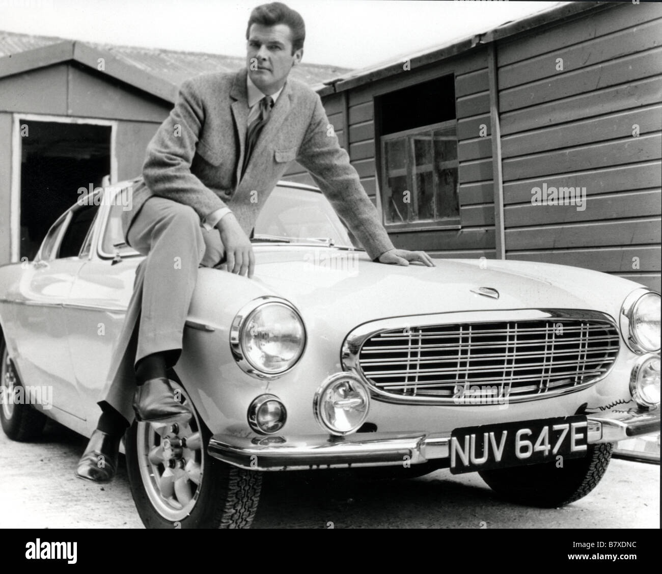 Roger Moore with the Volvo 1800  sports car for the TV serie The Saint This particular model registered as NUV647E - Stock Image