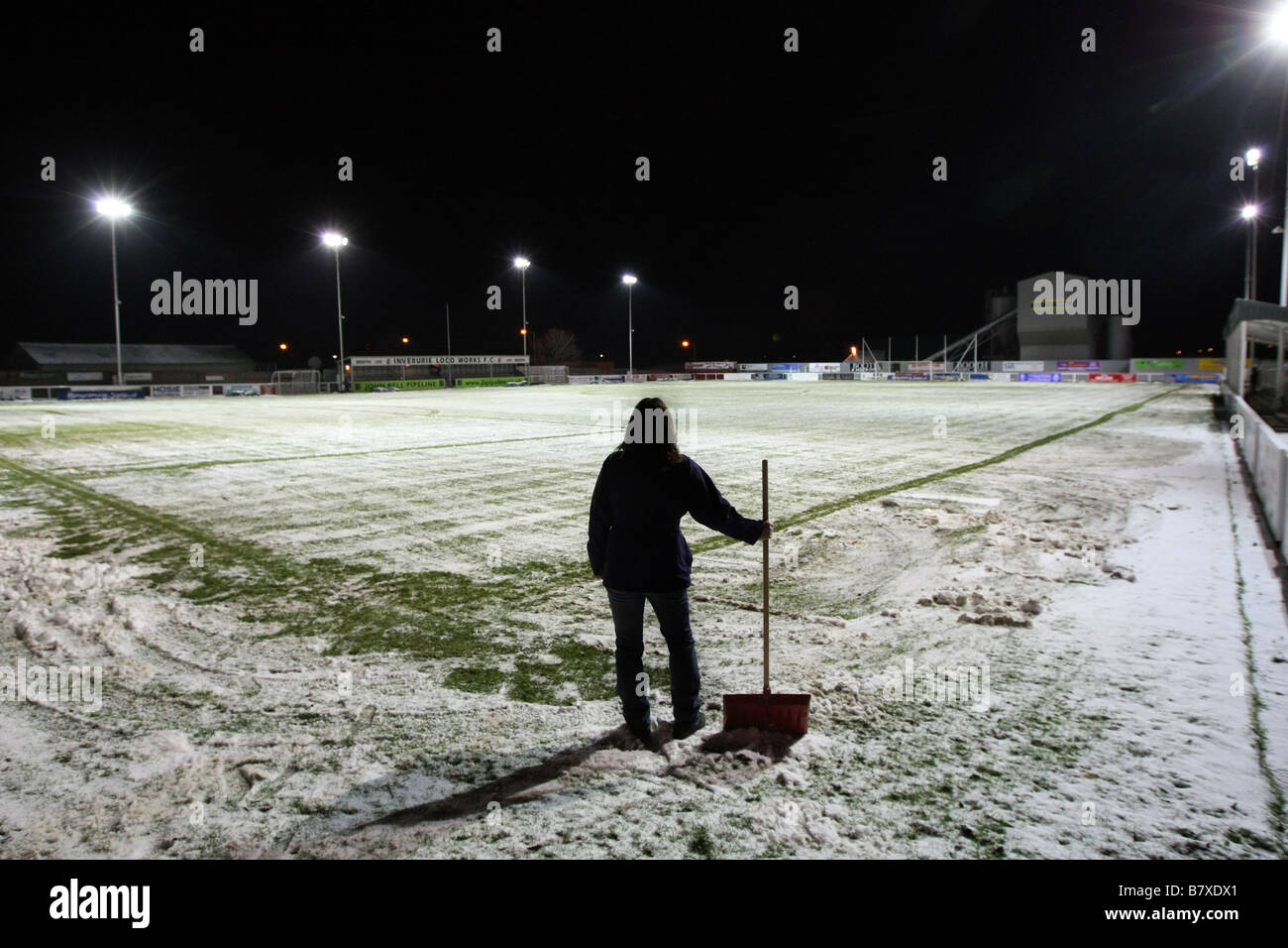 Scottish Highland League football pitch covered in snow during winter, with worker clearing lines and markers with - Stock Image