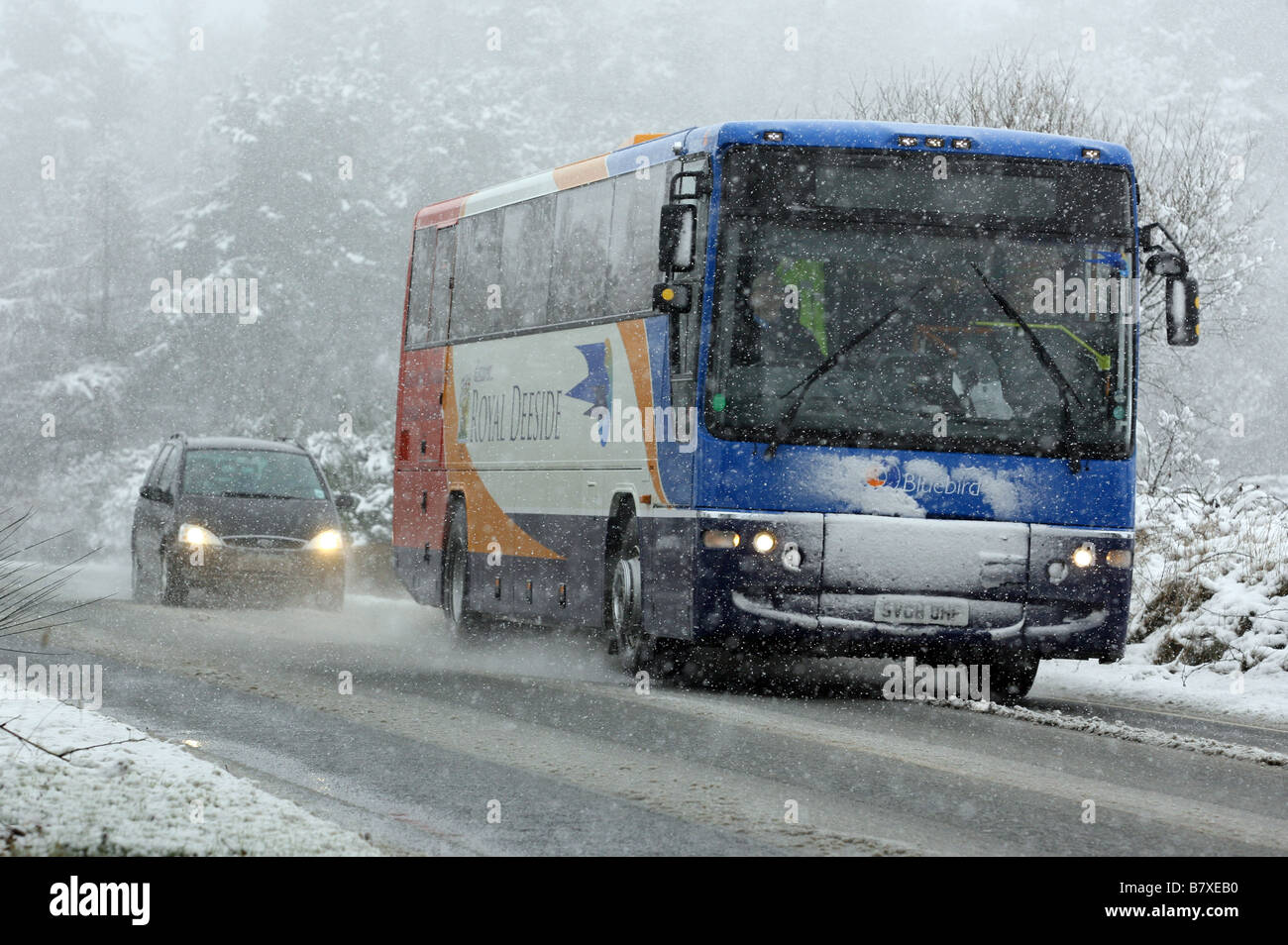 Stagecoach Bluebird bus driving along snow covered road in Rural Aberdeenshire, Scotland, UK - Stock Image