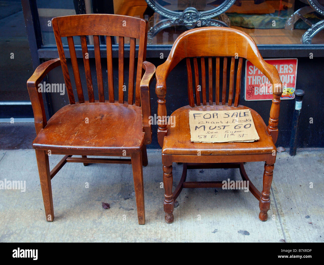 two old wooden chairs on a city sidewalk holding a handwritten stock