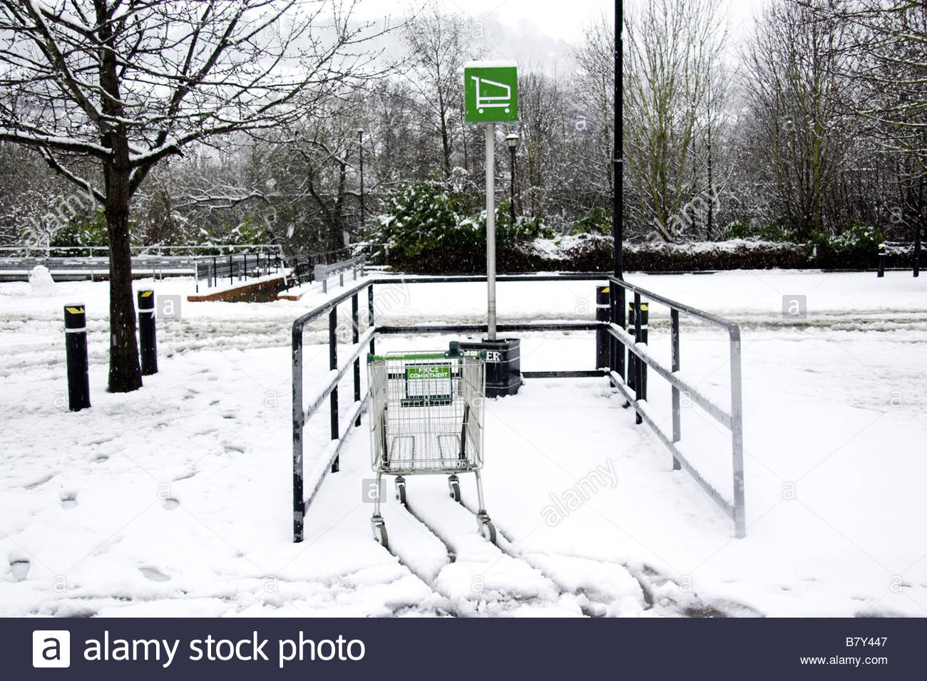 Lone shopping trolley in supermarket car park during bad weather, UK - Stock Image