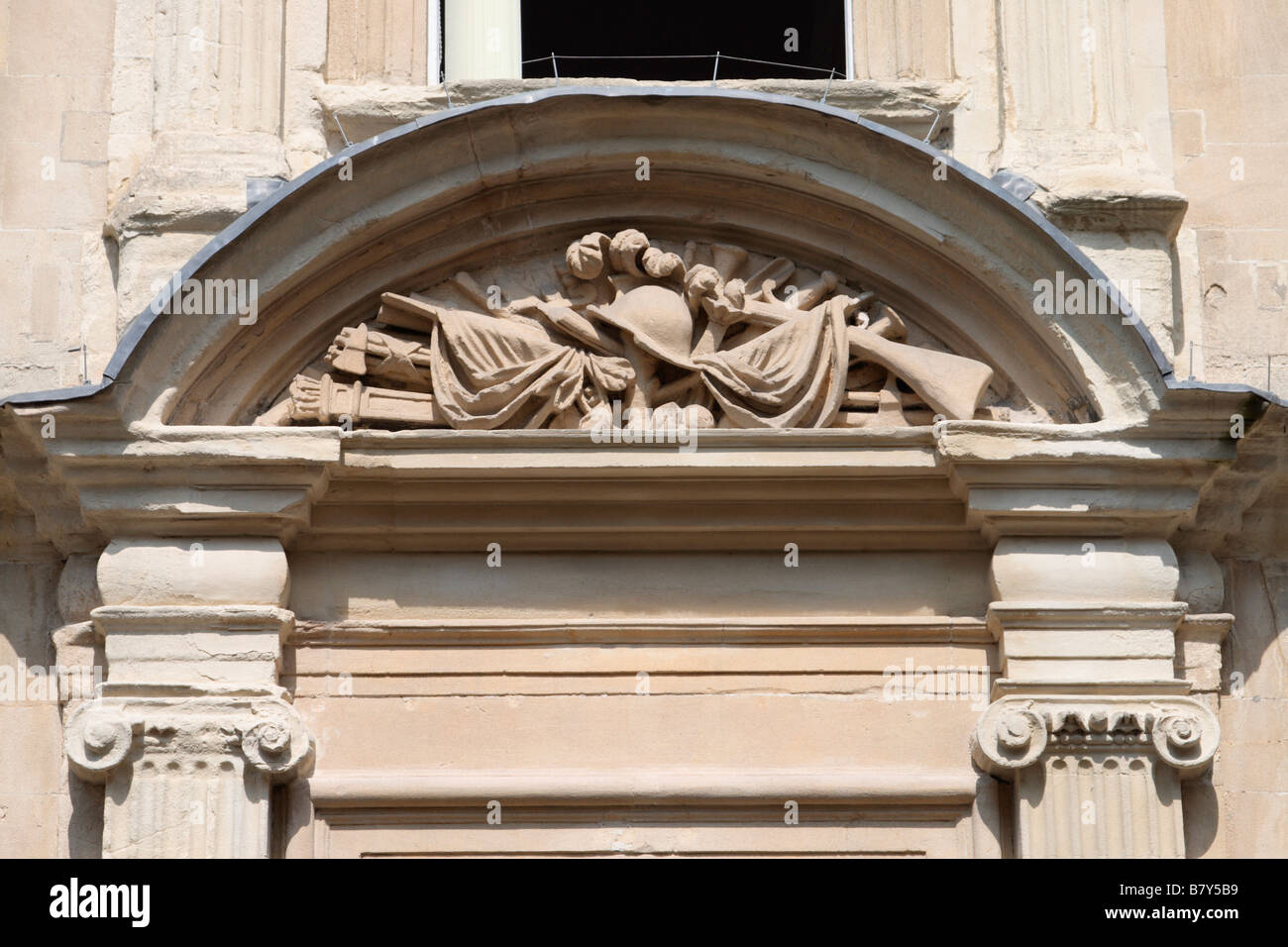 Carved stone architectural detail door of 5 Trim Street  Bath Somerset UK depicting military trophy, home of General - Stock Image