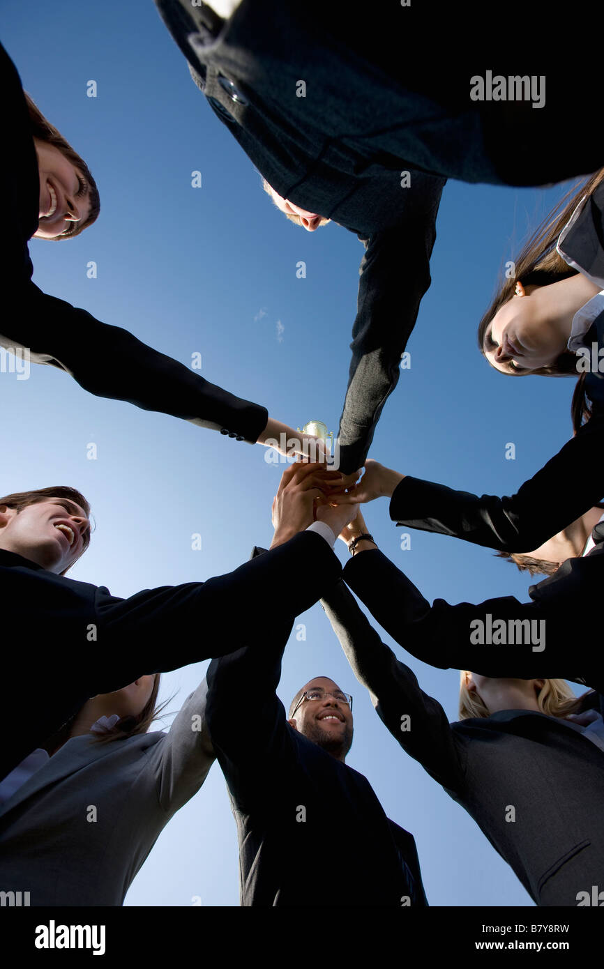 Group in business attire giving cheer - Stock Image
