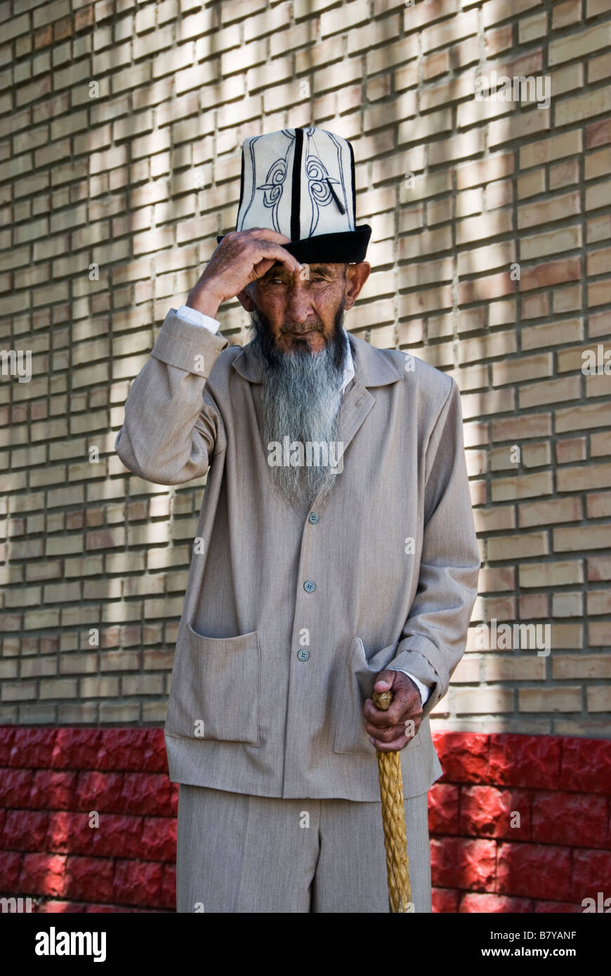 Old Kyrgyz man dressed with typical hat and walking stick Kochkor Kyrgyzstan - Stock Image