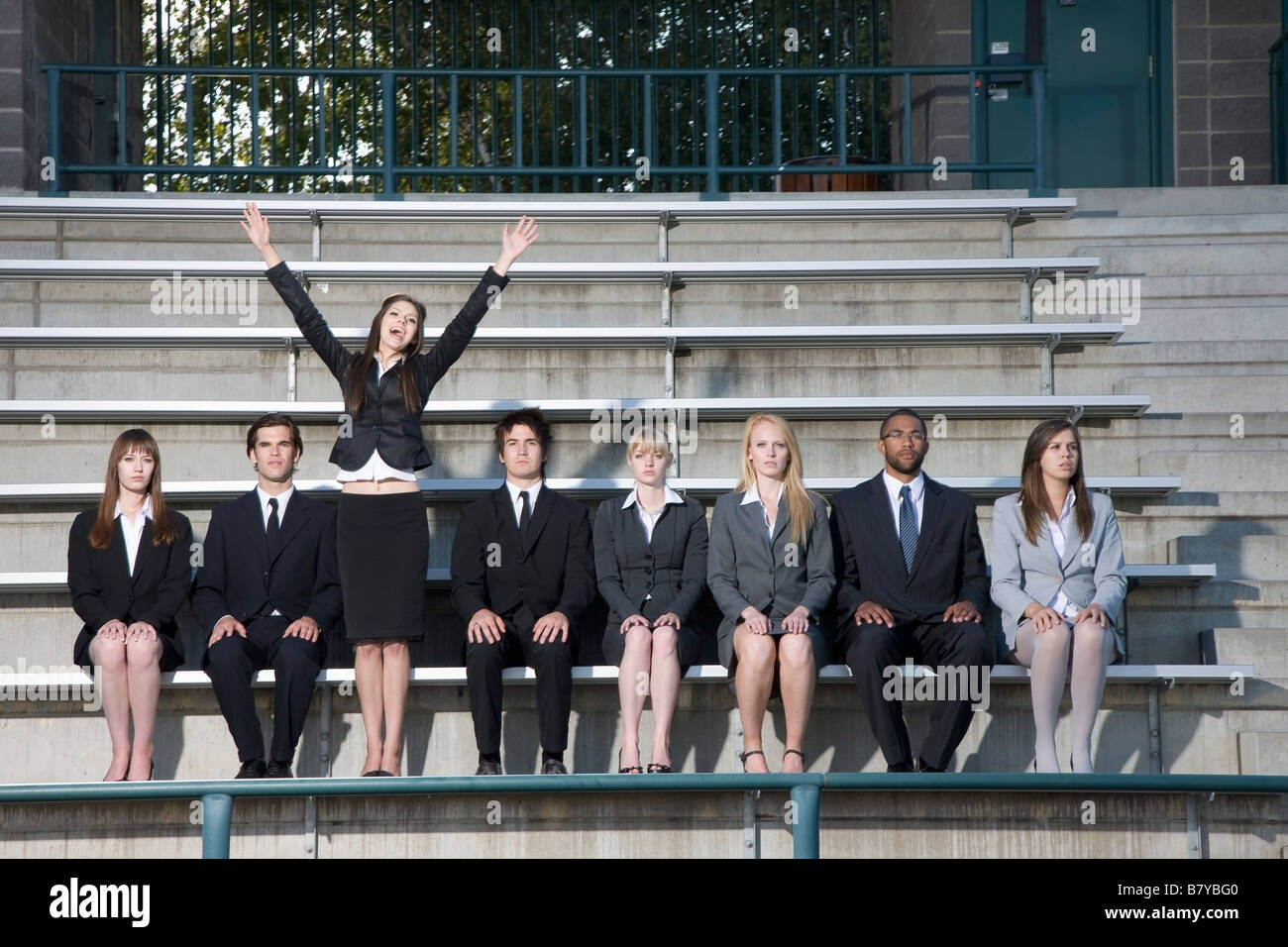 Businesswoman cheering in the stands among unmoving business people - Stock Image