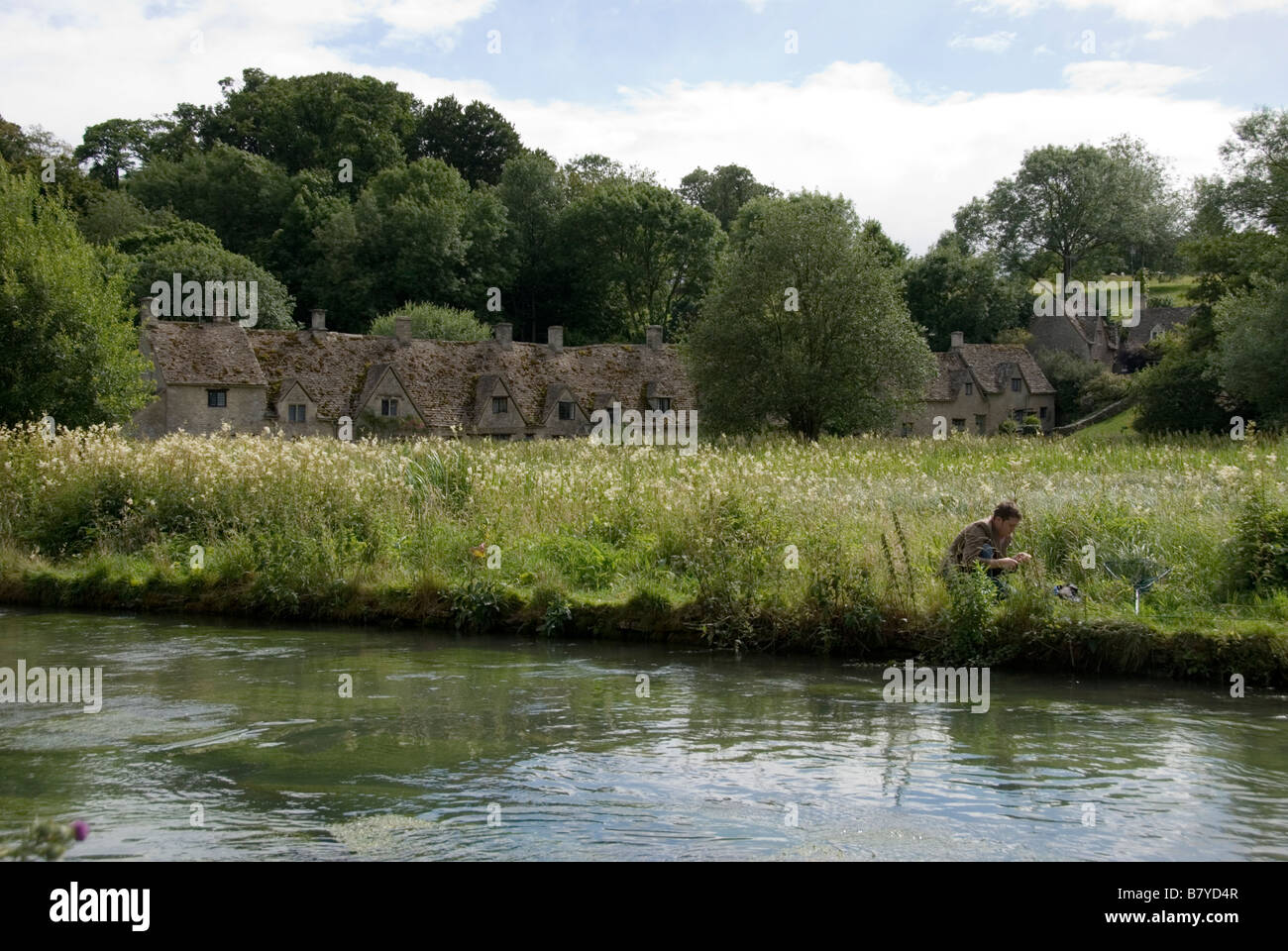 The Famous cottages of Arlington Row with a Trout Fisherman fishing in the river. - Stock Image