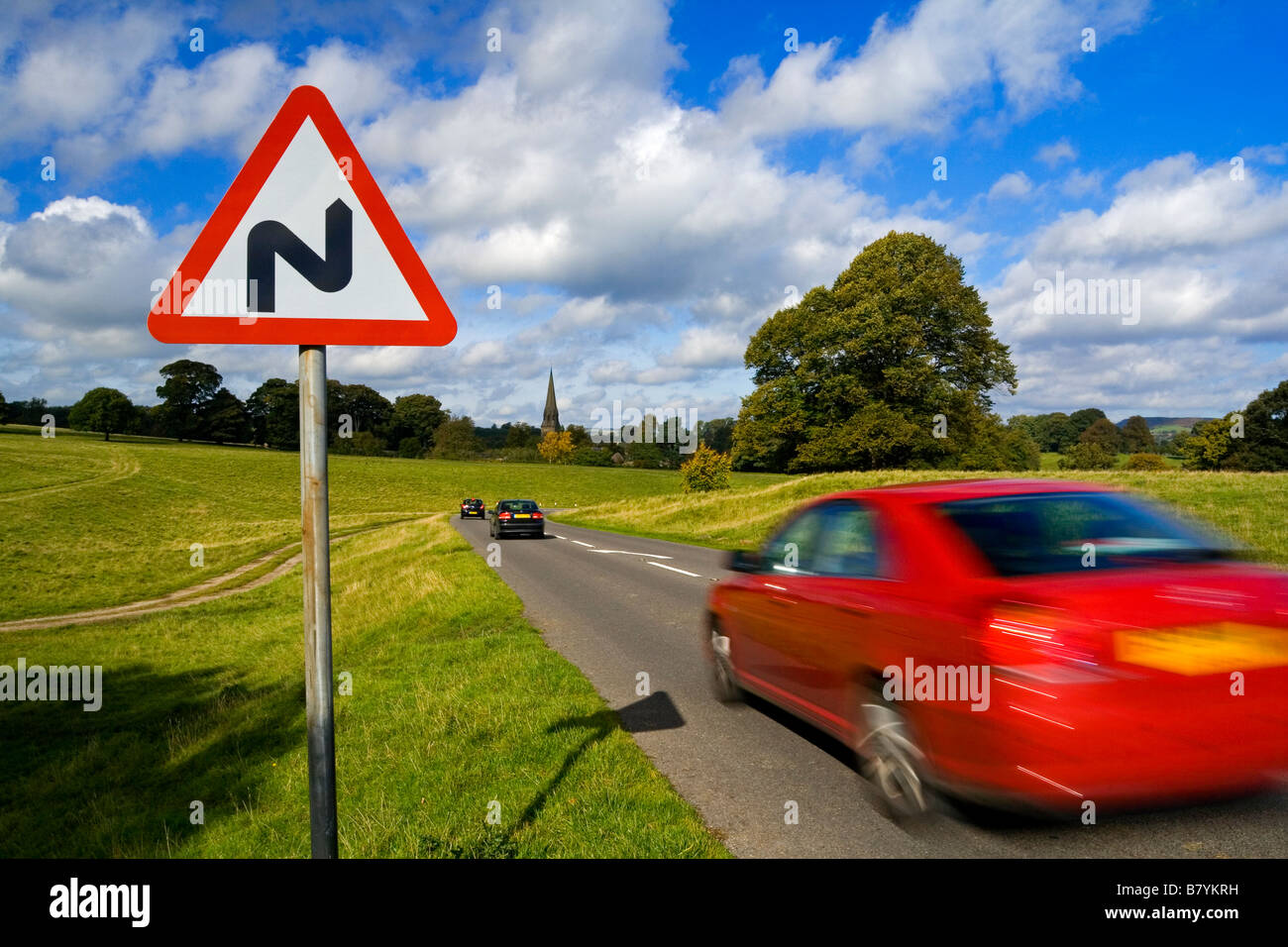 Red car driving past a triangular double bend warning sign on a country road Stock Photo