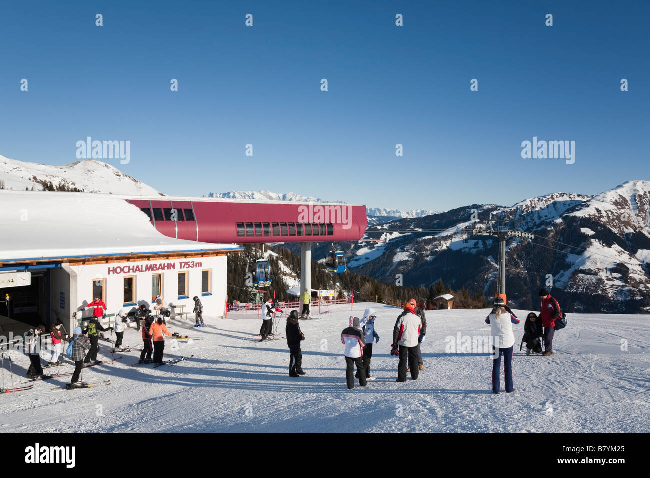 Skiers and walkers on piste snow slope by Hochalmbahn gondola station in Nationalpark Hohe Tauern in Austrian Alps. - Stock Image