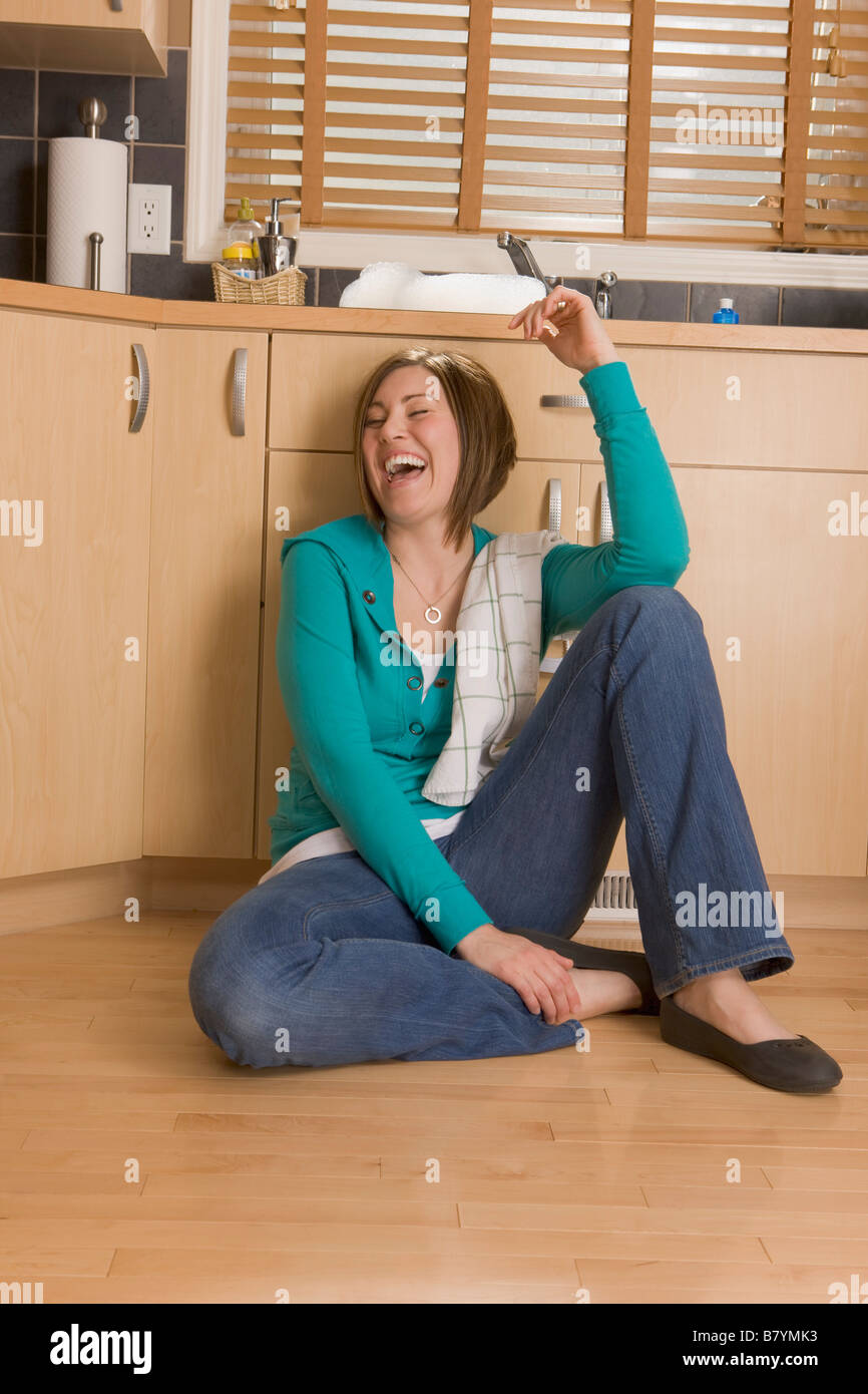 Woman laughing on the floor of the kitchen - Stock Image