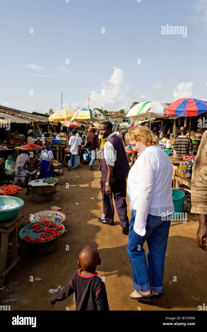 White woman walks through a Nigerian market on a hot sunny day and smiles at a small boy - Stock Image