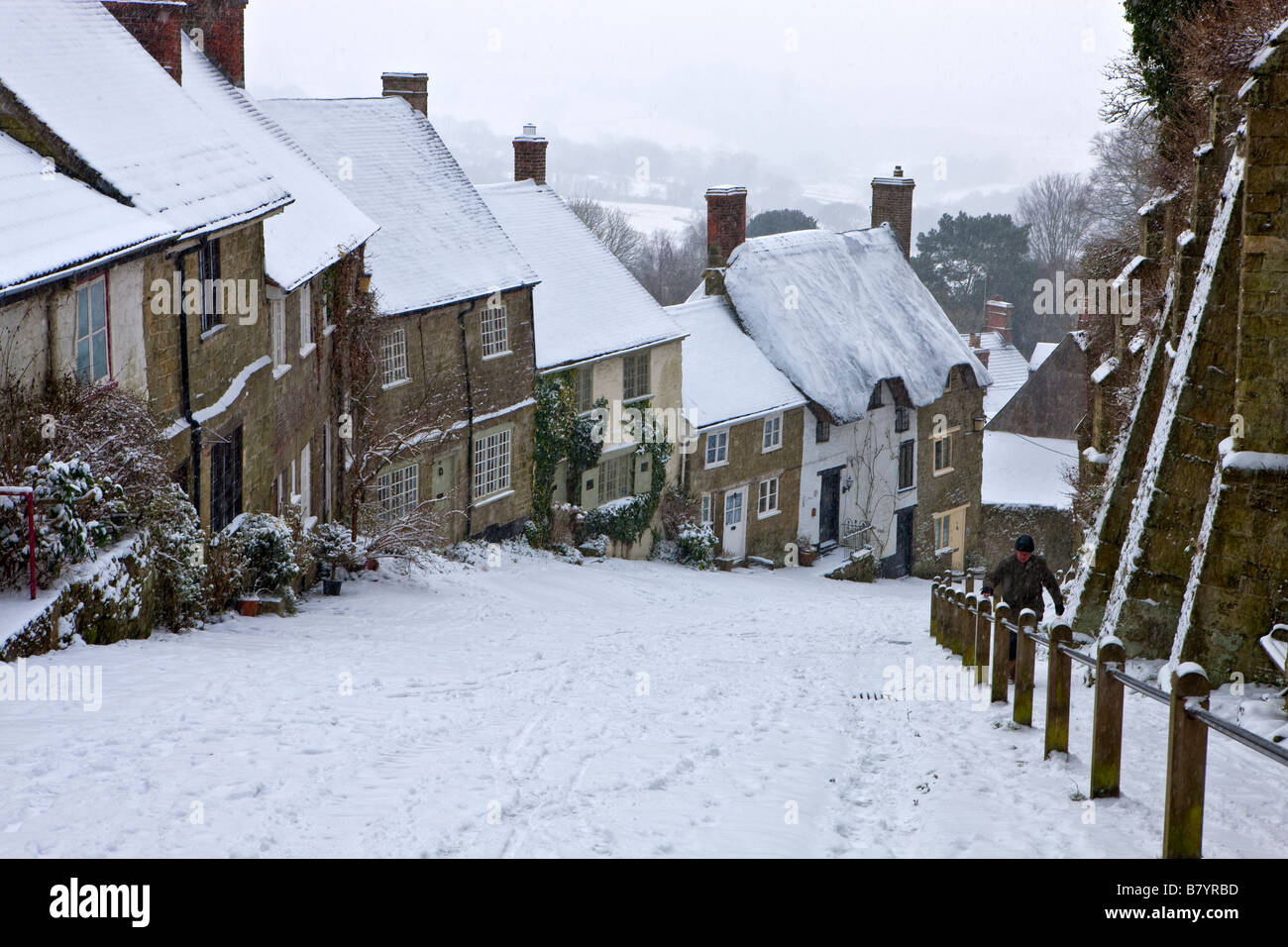 Gold Hill in the winter snow at Shaftesbury in Dorset, England - Stock Image